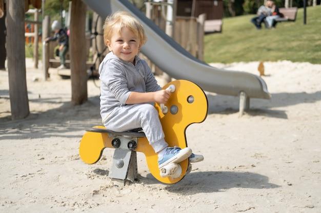 Kleine blanke blonde jongen spelen op kinderspeelplaats in een zonnige herfstdag.