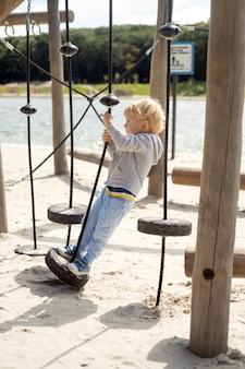 Kleine blanke blonde jongen spelen op kinderspeelplaats in een zonnige herfstdag