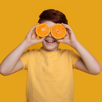 Kleine blanke gemberjongen bedekt zijn ogen met sinaasappels poseren in een t-shirt op een gele muur met vrije ruimte