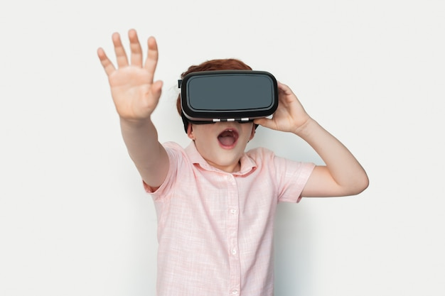 Kleine blanke gemberjongen die een virtual reality-headset draagt, raakt iets op een witte studiomuur aan