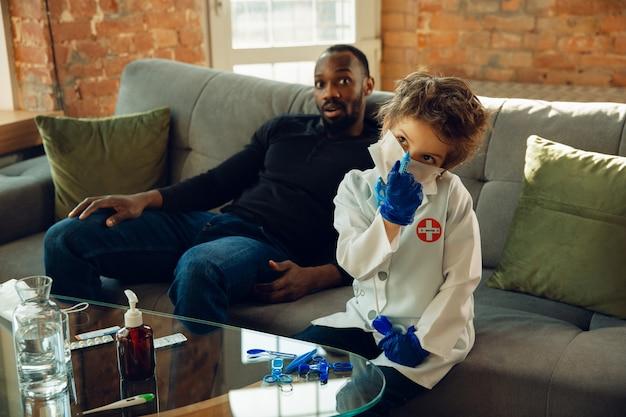 Kleine blanke jongen als arts die een patiënt raadpleegt die in een kast van dichtbij werkt