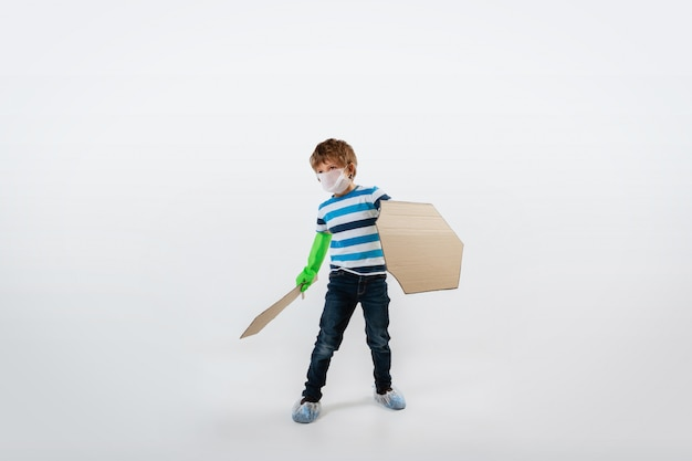 Kleine blanke jongen als een krijger in gevecht met een pandemie van het coronavirus, met een schild, een speer en een bandoleer van toiletpapier, aanvallend