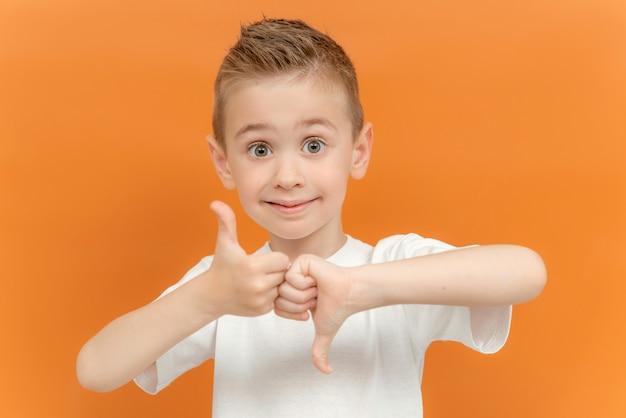 Kleine blanke jongen in witte t-shirt met duim op en neer gebaar in gebarentaal op geel