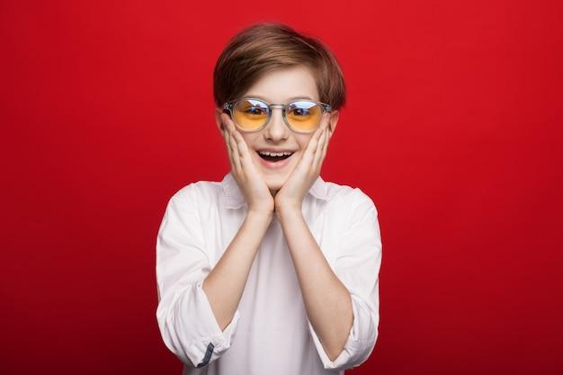 Kleine blanke jongen is verrast door iets wat zijn wangen aanraakt en glimlacht op een rode studiomuur