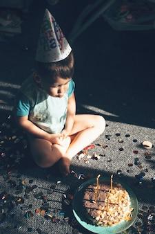 Kleine blanke jongen met feestmuts blaast de verjaardagslichten zittend op de vloer in de buurt van confetti