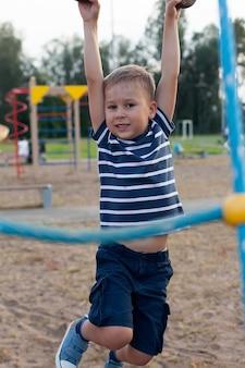 Kleine blanke jongen opknoping op de monkey bar door zijn hand om te oefenen op buitenspeeltuin.