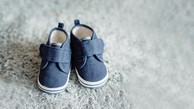 Kleine blauwe baby boy schoenen, douche uitnodiging concept zorg, pasgeboren, moederschap.