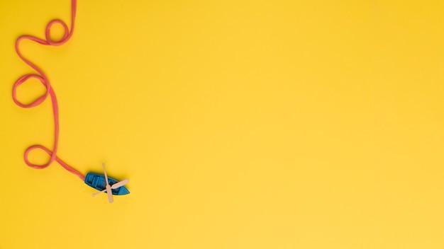 Kleine blauwe boot met oranje touw