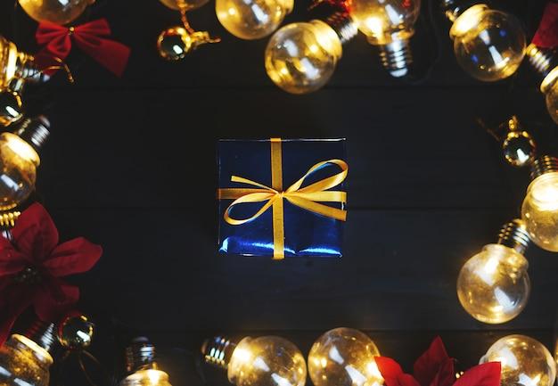 Kleine blauwe geschenk binnen gloeilampen en rode poinsettia op zwart hout. bovenaanzicht