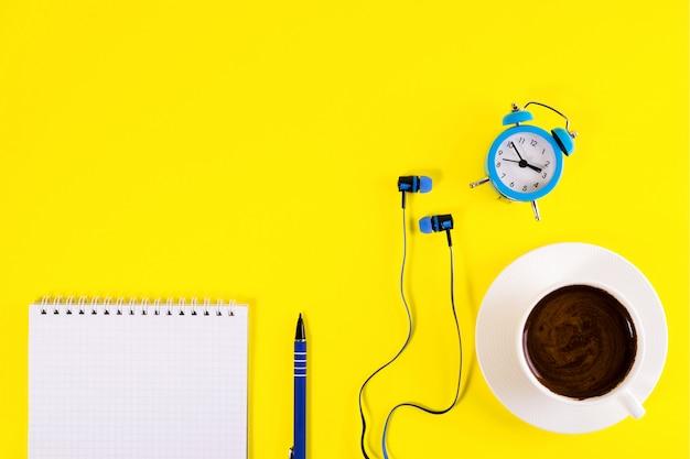 Kleine blauwe wekker, blauwe koptelefoon, kopje koffie en notitieboek met blauwe pen.