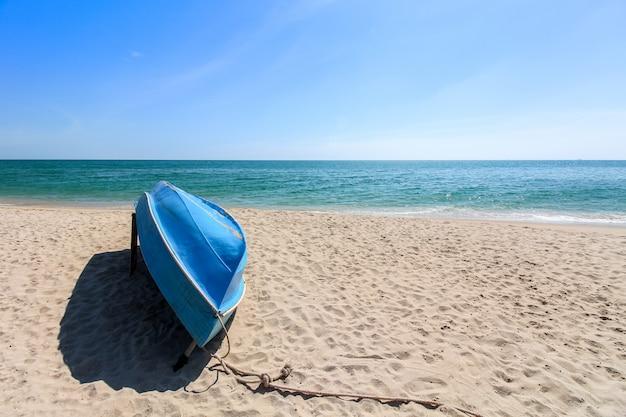 Kleine blauwe zeilboot ondersteboven legt op het strand