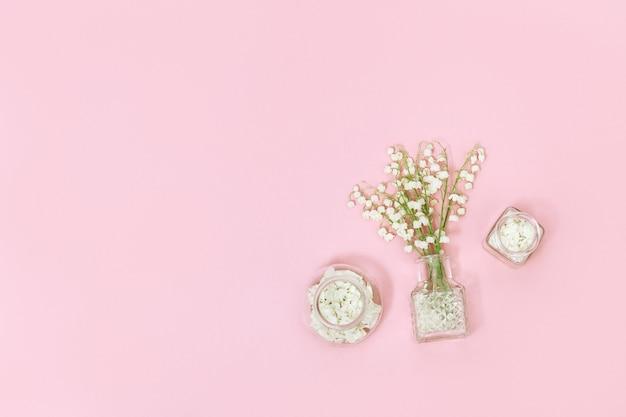 Kleine bloemen en glazen fles met droge bloemblaadjes