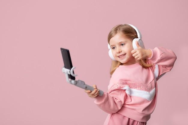 Kleine blogger-influencer neemt video's op van de blog op een smartphone, communiceert met abonnees, plaatst likes, luistert naar muziek met een koptelefoon, leren op afstand op een geïsoleerde muur.