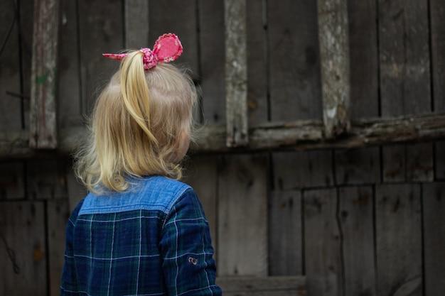 Kleine blonde baby staat met zijn rug tegen de achtergrond van de oude houten hek.