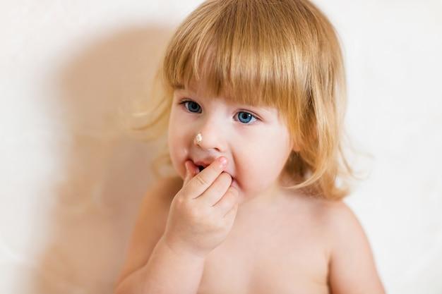 Kleine blonde babymeisje in roze broek zittend op witte tafel verjaardagstaart eten