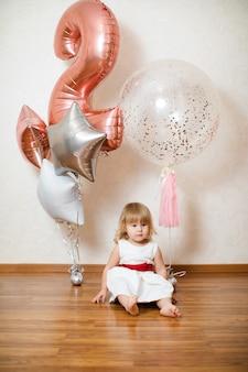 Kleine blonde babymeisje met grote roze en witte ballonnen op haar verjaardag