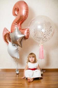 Kleine blonde babymeisje twee jaar oud met grote roze en witte ballonnen op haar verjaardagsfeestje.