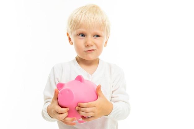 Kleine blonde blanke jongen met roze geïsoleerd varken spaarpot