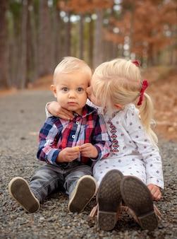 Kleine blonde broers en zussen knuffelen en zitten op de grond in een bos in texas