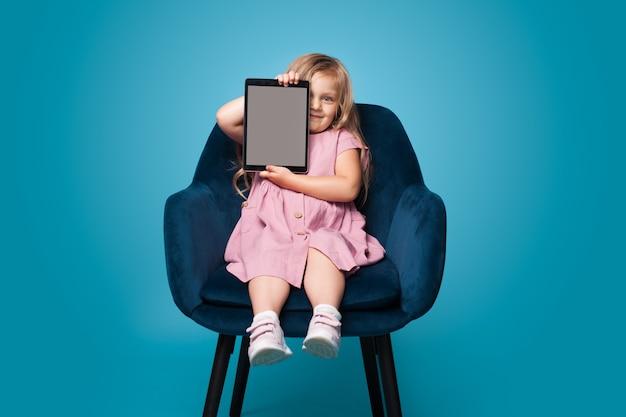 Kleine blonde dame zittend in de stoel op een blauwe muur toont een tablet met vrije ruimte om iets te promoten