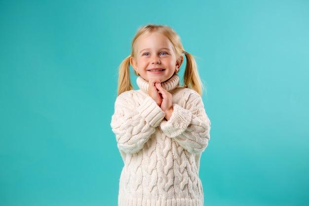Kleine blonde in trui lachend op blauw