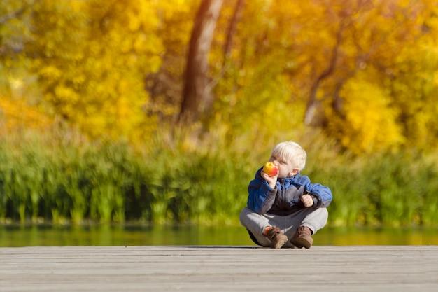 Kleine blonde jongen die een appel op het dok eet
