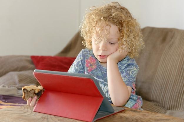 Kleine blonde jongen die tabletcomputer met behulp van