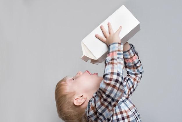 Kleine blonde jongen drinkt uit een groot wit pakket