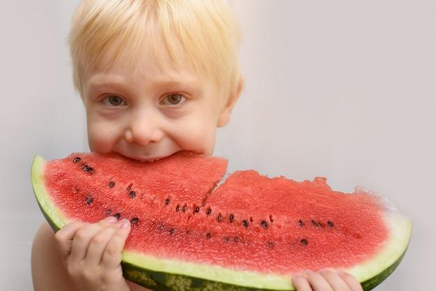 Kleine blonde jongen eet een groot stuk watermeloen.