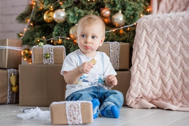 Kleine blonde jongen eet een peperkoek man bij de kerstboom thuis.