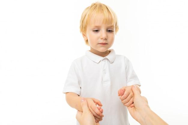Kleine blonde jongen hand in hand op witte muur