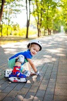 Kleine blonde jongen in witte sporthelm en blauw t-shirt rijden op de rolschaatsen