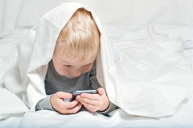 Kleine blonde jongen kijkt naar iets op een smartphone. liggend in bed en verstopt onder de dekens.