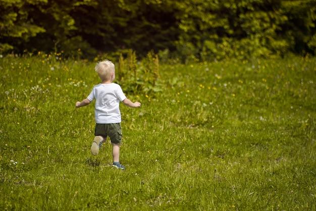 Kleine blonde jongen loopt in een groene weide aan de rand van het bos