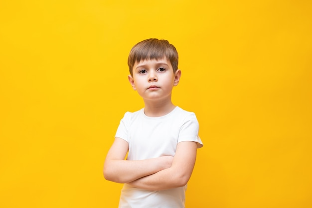 Kleine blonde jongen met bruine ogen van 5-6 jaar oud in een stijlvol wit poloshirt, armen gevouwen op zijn borst, geïsoleerd op een gele muur