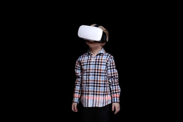 Kleine blonde jongen met een bril van virtual reality. geruite overhemd. zwart