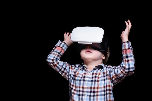 Kleine blonde jongen met een bril van virtual reality kijkt omhoog. geruite overhemd. zwart