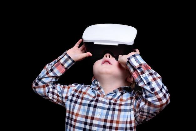 Kleine blonde jongen met een bril van virtual reality kijkt omhoog. geruite overhemd