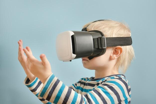 Kleine blonde jongen met een bril van virtual reality.