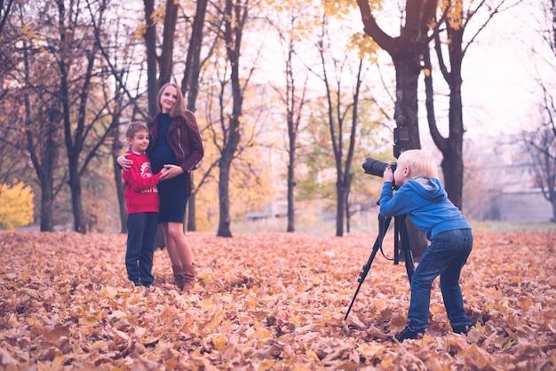 Kleine blonde jongen met een grote fotocamera op een statief.