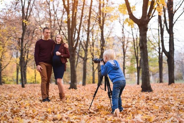 Kleine blonde jongen met een grote slr-camera op een statief