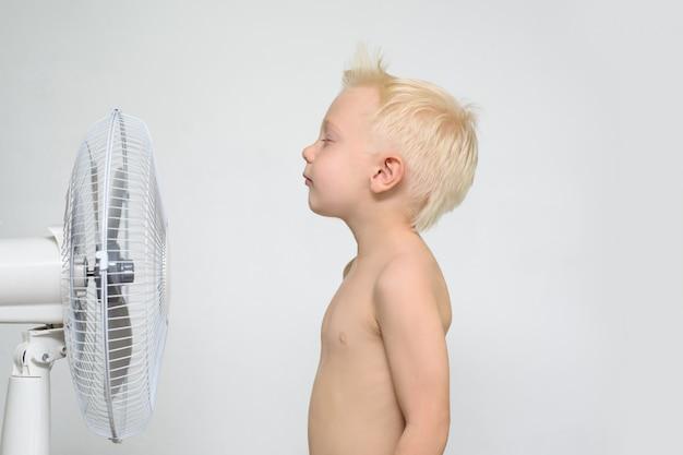 Kleine blonde jongen met naakte torso en gesloten ogen staat in de buurt van een ventilator. zomer concept