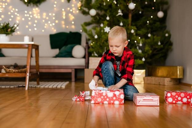 Kleine blonde jongen pak cadeaus thuis uit