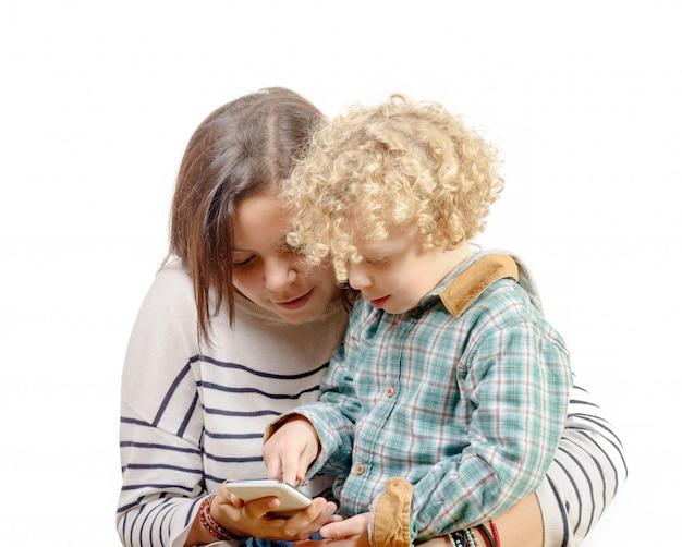 Kleine blonde jongen speelt met de telefoon van zijn zus