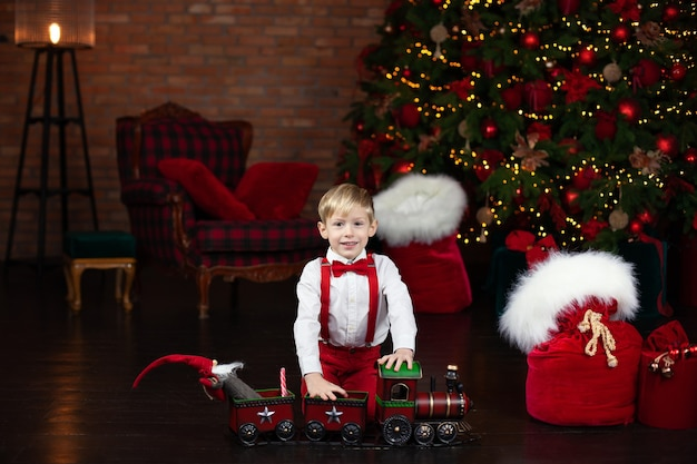 Kleine blonde jongen speelt met een rode stoomtrein speelgoed in huis