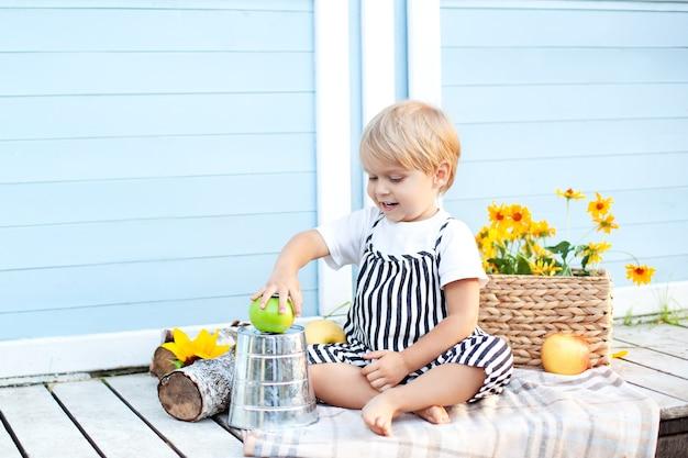 Kleine blonde jongen zittend op een houten veranda thuis en eet een appel gelukkig kind en fruit