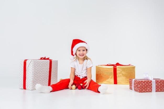Kleine blonde kinderen in santas hoed zitten tussen geschenkdozen en spelen met kerstballen