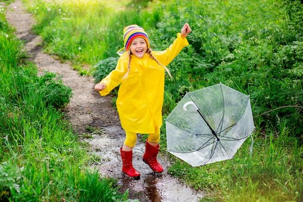 Kleine blonde meisje glimlacht springt op plassen in het voorjaar in gele regenjas en rubberen laarzen met paraplu