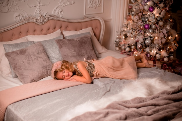 Kleine blonde meisje in bed naast de kerstboom. kerstavond