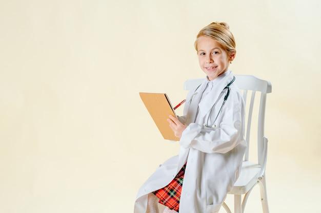 Kleine blonde meisje in een pak van een arts maakt een notitie in een notitieblok